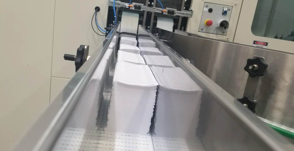 Napkins coming out of converting equipment on conveyor belt